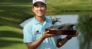 Michael Kim celebrates with the trophy after winning the John Deere Classic. Photograph: Streeta Lecker/Getty