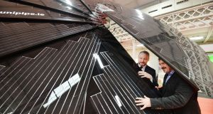 Jim Gannon Chief Executive SEAI and Paul O'Donnell MD of Unipipe examine a Solar Smart Flower. Photograph: Alan Betson
