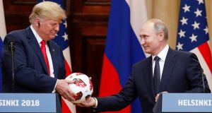 US president Donald Trump receives a football from Russian president Vladimir Putin at a joint news conference after their meeting in Helsinki, Finland. Photograph:  Grigory Dukor/Reuters