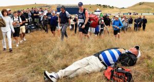A spectator sleeps in the grass as Pádraig Harrington passes by during the Scottish Open at Gullane GC  in Gullane, Scotland. Photograph:  Andrew Redington/Getty