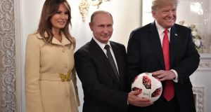 Russian president Vladimir Putin (centre), US president Donald Trump (right) and US first lady Melania Trump (left) pose with a soccer ball of the 2018 FIFA World Cup during their meeting in the Presidential Palace in Helsinki, Finland. Photograph: Alexei Nikolsky/Sputnik/EPA