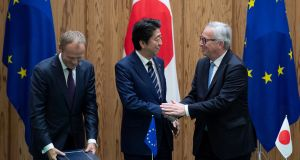 Japanese prime minister Shinzo Abe shakes hands with European Commission president Jean-Claude Juncker and European Council president Donald Tusk after signing the trade deal. Photograph: Martin Bureau/Pool via Reuters