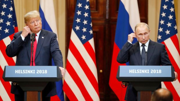 US president Donald Trump and Russian president Vladimir Putin adjust their earpiece plugs during a joint press conference following their summit talks in Helsinki, Finland. Photograph: Anatoly Maltse/EPA