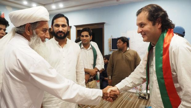 Walid Iqbal (R), grandson of national poet Muhammad Iqbal and a candidate for Imran Khan's Tehreek-e-Insaf party in the election in Pakistan, greets a local religious leader in Javed Colony, Lahore. Photograph: Lorraine Mallinder