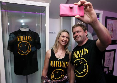 Nirvana fans Tanya and Dave Deegan from Dublin take a picture alongside Kurt Cobain's Nirvana smiley face t-shirt at the opening of the 'Growing Up Kurt' exhibition. Photograph: Brian Lawless/PA Wire