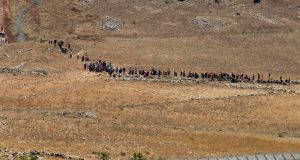A picture taken  from the Israeli-annexed Syrian Golan Heights shows displaced Syrians going back to their camp near the Syrian village of Burayqah, after being turned back by the Israeli forces at the border fence between Syria and the  Golan Heights, where they were trying to seek refuge.  Photograph: Jalaa Marey/AFP/Getty Images
