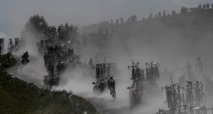 DUST AND SWEAT: France's Fabien Grellier (centre) ascends the Plateau des Glieres during the 10th stage of the 105th edition of the Tour de France, between Annecy and Le Grand-Bornand, in the French Alps. Photograph: Jeff Pachoud/AFP/Getty Images