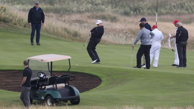 Trump attempts to steer a putt into the hole during his round. Photo: Andrew Milligan/PA Wire