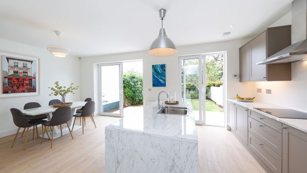 Kevin Houlihan knocked the dividing wall between the kitchen and the dining room to create a modern space the width of the house that had room for a decent dining table as well as a long stone-topped island.