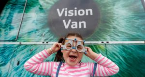 ONE VISION: Ella Dunne (5) from Ballyfermot in front of the Vision Express' mobile Vision Van at Liffey Valley Shopping Centre which was offering free eye tests to members of the public. Photograph: Andres Poveda