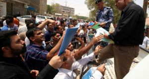 Iraqi protesters hand over job requests to government employees in Basra, Iraq. Photograph: Essam al-Sudani/Reuters