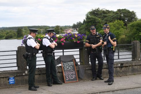 BORDER BANTER: PSNI officers chat with gardaí next to a sign left by tourists at the Border in St Belleek, Co Fermanagh. Photograph: Clodagh Kilcoyne/Reuters