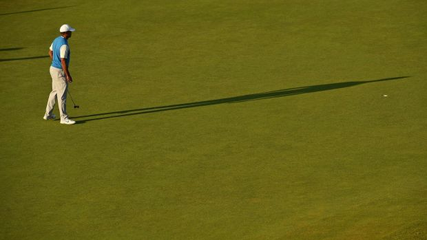 Tiger Woods checks the line of his putt on the 17th. Photo: Glyn Kirk/Getty Images