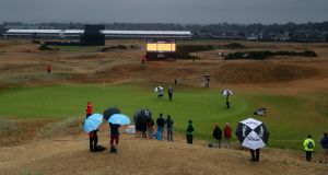 Fans shelter from rain as they watch the action on the 2nd green during day two of The Open Championship 2018 at Carnoustie Golf Links. Photo: David Davies/PA Wire