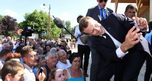 PRESIDENTIAL: French president Emmanuel Macron takes a selfie of members of the public as he arrives for the inauguration of the new public services building in Sarliac-sur-l'Iles, southwestern France, during a visit to the Dordogne region, this week. Photo: Nicolas Tucat/Getty Images