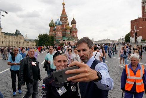 LOOKALIKE:  Gareth Southgate lookalike Neil Rowe poses for a selfie with a tourist police officer  in Moscow last weekend.  Photo: Christopher Furlong/Getty Images