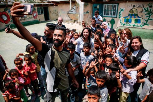 WEST BANK: Palestinian youths take selfies alongside children from the Bedouin village of Khan al-Ahmar in the occupied West Bank, during the Palestinian prime minister's visit to the village on July 14th. Israel's supreme court issued an order temporarily suspending the evacuation of residents from a Palestinian Bedouin village in the occupied West Bank, expected to be demolished in the coming days. Photo: Getty Images