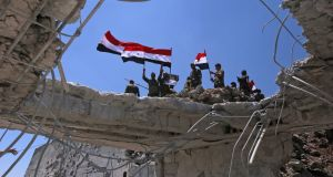 Syrian government forces' soldiers wave their national flags after taking back the city of Quneitra. Photograph: AFP