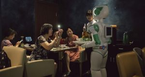 Diners take pictures of the robot waiter at Robot Magic Restaurant in Shanghai, June 27, 2018. Photograph: Yuyang Liu/The New York Times