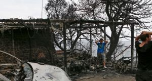 Residents react as they look at their burned house following a wildfire in Mati, a northeastern suburb of Athens. Photograph: EPA