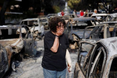 BURNT OUT: A distraught woman searches for her dog after a devastating wildfire at the village of Mati, near Athens, Greece. At time of publishing at least 74 people are known to have died in Greek wildfires, amid an ongoing heatwave. Photograph: Costas Baltas/Reuters