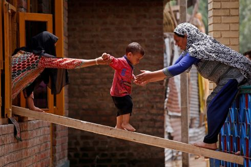 IN SAFE HANDS: Women help a child to cross on a plank of wood to another house after flash floods in Tailbal, on the outskirts of Srinagar, the summer capital of the Indian state of Jammu and Kashmir. Photograph: Danish Ismail/Reuters