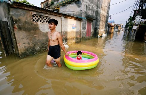 HEAD ABOVE WATER: A man pulls his daughter along in an inflatable paddling pool at a flooded village after heavy rainfall caused by tropical storm Son Tinh, outside Hanoi, Vietnam. Photograph: Kham/Reuters