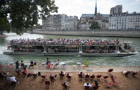 SUMMER IN PARIS: People watch from a boardwalk on the River Seine in Paris as a bateau-mouche (tour boat) glides by near the Ile de la Cite during the 17th edition of the Paris Plage (Paris beach) summer event. Photograph: Gerard Julien/AFP/Getty Images