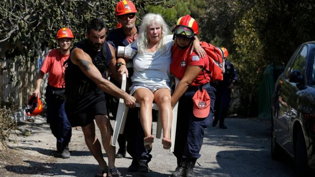 Members of a rescue team carry an injured woman in Mati, Greece on Wednesday. Photograph: Thanassis Stavrakis/AP