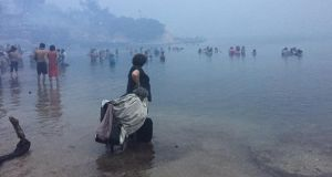 People stand by the shore as a wildfire burns in Mati, Greece on Monday. Photograph:  Kalogerikos Nikos/via Reuters