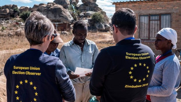 Members of a European Union election observation team speak to voters in Nyatsime, Zimbabwe. Photograph: Marco Longari/AFP/Getty Images
