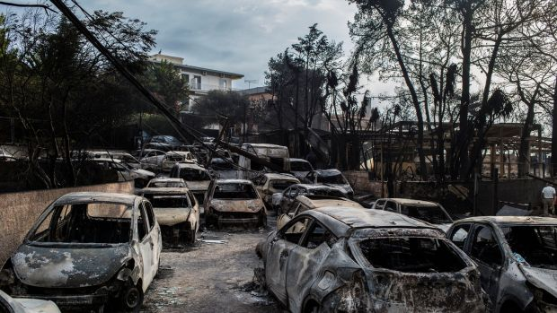 Burnt-out cars in Greece after flames had swept through. Photograph: Getty Images