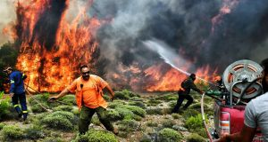 Firefighters and volunteers fighting flames  at the village of Kineta near Athens, Greece. Terrified residents fled to the sea to escape the flames. Photograph: Getty Images