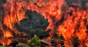 Firefighters try to extinguish flames during a wildfire at the village of Kineta, near Athens, on July 24th, 2018.  Photograph: Valerie Gache/AFP/Getty Images