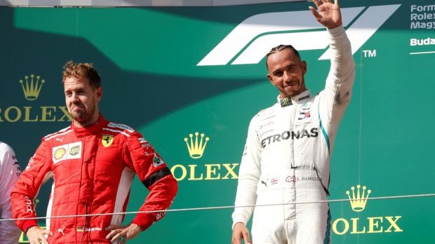 Lewis Hamilton celebrates on the podium alongside second place Sebastian Vettel. Photograph: Bernadett Szabo/Reuters