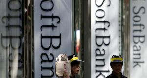 Employees of SoftBank Corp work outside its branch in Tokyo, Japan. Photograph: Yuya Shino/Reuters/File Photo