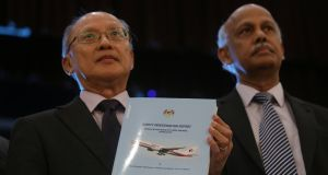 Investigator-in-charge Kok Soo Chon shows the MH370 safety investigation report booklet to the media after a news conference in Putrajaya, Malaysia on July 30th, 2018. Photograph: Reuters/Sadiq Asyraf