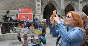 Tourists at the Molly Malone statue in St Andrew's Street in Dublin. Photograph: Alan Betson