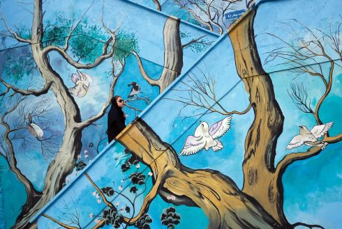 WINGS OF A DOVE: A woman walks up steps decorated with dove-themed murals in Tehran, Iran. Photograph: Abedin Taherkenareh/EPA