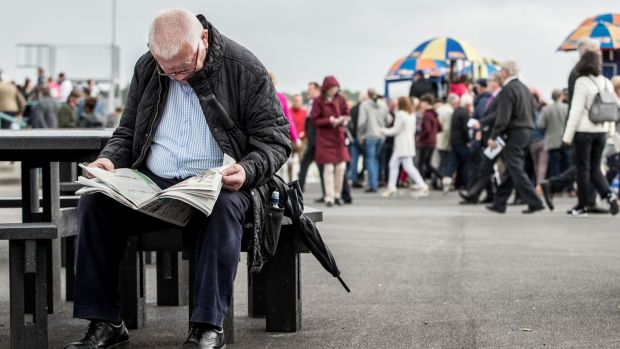 A punter reads in on the second day of the Galway Racing Festival at Ballybrit. Photograph: James Crombie/Inpho