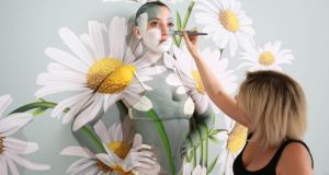 Model promotion: Daisy Lowe is camouflaged into a wall of daisies by artist Carolyn Roper to publicise Samsung's 'ambient mode' television screens. Photograph: Matt Alexander/PA