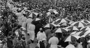 Pope John Paul II's visit to Ballybrit Racecourse in Galway in 1979. Escorts hold umbrellas over the priests who are administering Holy Communion.