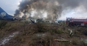 Firefighters douse a fire as smoke billows above the site where an Aeromexico passenger jet crashed in Mexico's northern state of Durango. Photograph: Proteccion Civil Durango/via Reuters