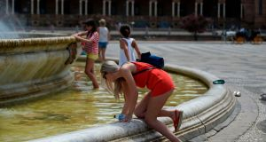 A woman refreshes herself in a fountain at Plaza de Espana in Sevilla as a heatwave hits Spain and Portugal. Photograph: Cristina Quicler/AFP/Getty Images