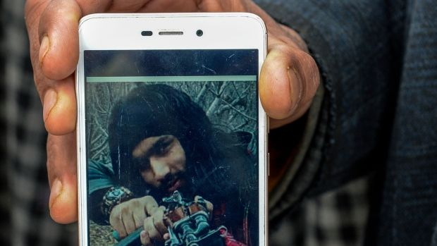 "Mohammed Maqbool Bhat shows a picture of his son, Sameer Tiger, who joined Hizbul Mujahedeen, an outlawed Kashmiri separatist group. Soon, his image started popping up on separatist websites. ""When we saw that,"" Maqbool said, ""we said goodbye."" Photograph: Atul Loke/New York Times"