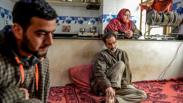 Mohamad Altaf, (centre), who was shot once in the back of his right knee by Sameer Tiger, and his wife Fareeda Akhtar at their home in Qasbayar, India, in the state of Kashmir. Photograph: Atul Loke/New York Times