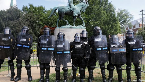 Virginia State Police in riot gear stand in front of the statue of General Robert E Lee before forcing white nationalists, neo-Nazis and members of the 'alt-right' out of Emancipation Park after the 'Unite the Right' rally was declared an unlawful gathering August 12th, 2017 in Charlottesville. Photograph: Chip Somodevilla/Getty Images