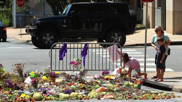 Seven year-old Lily Holtz places flowers on the street where Heather Heyer was killed and 19 others injured when a car slammed into a crowd on August 18th, 2017 in Charlottesville, Virginia. Photograph: Mark Wilson/Getty Images