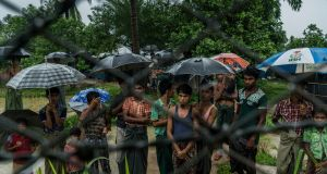 Rohingya Muslims behind barbed wire in the Taung Pyo border area where they are stranded between Myanmar and Bangladesh. Photograph: Adam Dean/The New York Times