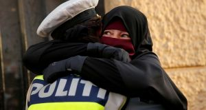 A wearer of the niqab weeps as she is embraced by a police officer during a demonstration against the Danish face veil ban in Copenhagen. Photograph: Reuters